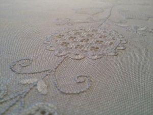 Bild einer Tischdecke mit gesticktem Blumen-Muster.
